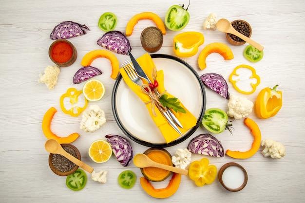 Bovenaanzicht gebonden mes en vork met gele servet op witte schotel gesneden groenten rode kool pompoen bloemkool gele paprika kruiden in kleine kommen op witte tafel