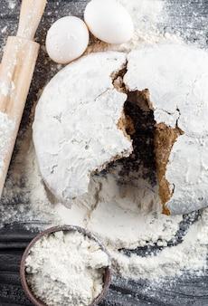 Bovenaanzicht gebroken cake met deegroller, meel, eieren op donkere houten oppervlak. verticaal