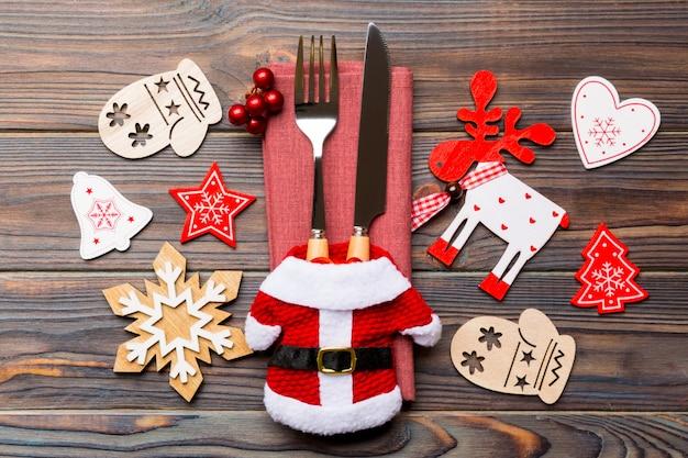Bovenaanzicht gebruiksvoorwerpen op servet met vakantie decoraties en rendieren op hout