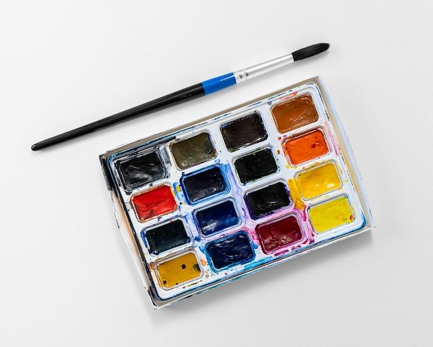 Bovenaanzicht gebruikte kleurenpaletdoos en kwast