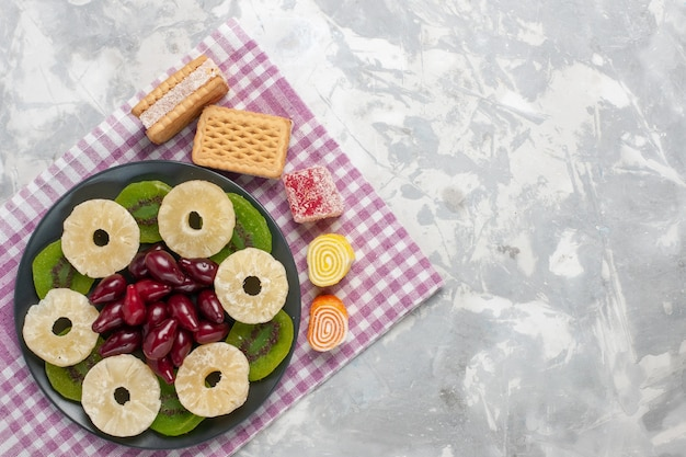 Bovenaanzicht gedroogd fruit ananas ringen kornoeljes en kiwi plakjes op witte achtergrond fruit droge zoete suiker zuur
