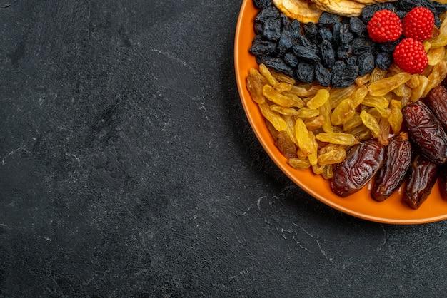 Bovenaanzicht gedroogd fruit met rozijnen in plaat op donkergrijze ruimte