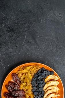Bovenaanzicht gedroogd fruit met rozijnen in plaat op grijs bureau