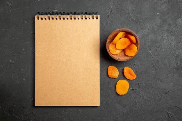 Bovenaanzicht gedroogde abrikozenrozijnen met notitieblok op donkere ondergrond droge fruitrozijnen