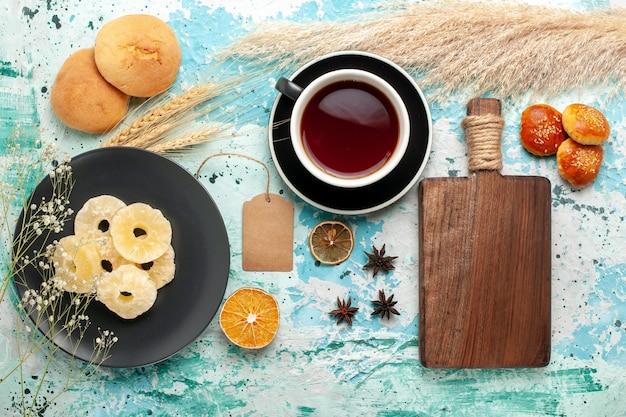 Bovenaanzicht gedroogde ananas ringen met kopje thee en koekjes op blauwe achtergrond cake bakken fruit koekjes zoete suiker koekjes