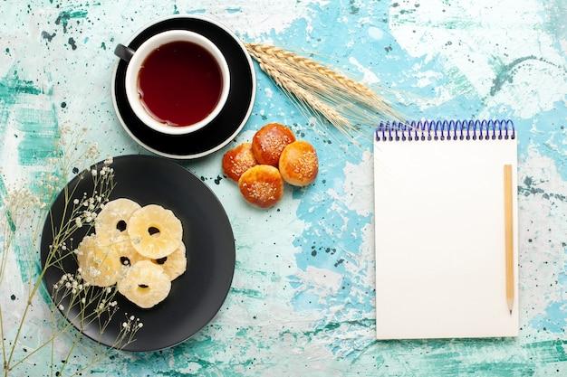 Bovenaanzicht gedroogde ananasringen binnen plaat met gebak en kopje thee op het blauwe bureau fruit ananas droge zoete suiker