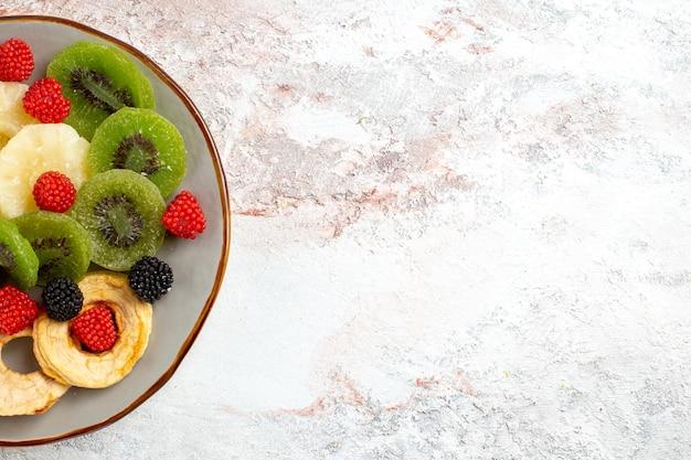 Bovenaanzicht gedroogde ananasringen met gedroogde kiwi's en appels op het witte bureau