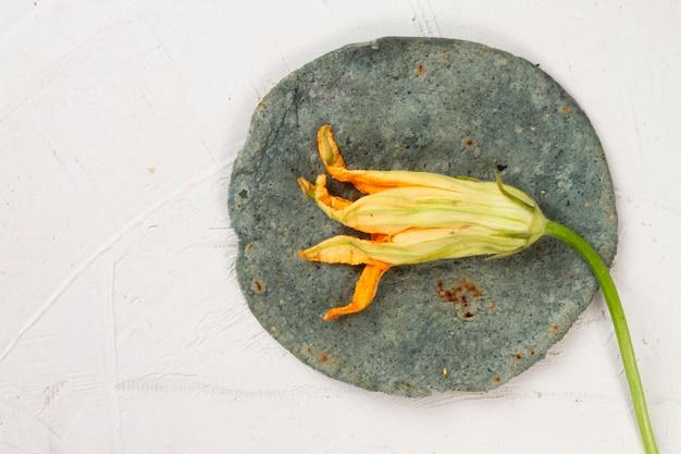 Bovenaanzicht gedroogde bloem over spinazietortilla