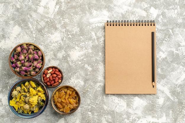 Bovenaanzicht gedroogde bloemen met noten en rozijnen op witte achtergrond noten rozijnen bloem plant