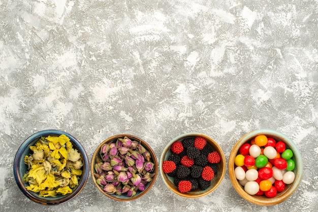 Bovenaanzicht gedroogde bloemen met snoepjes en bessen confitures op witte achtergrond candy koekje thee suiker koekje zoet