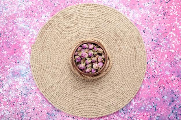 Bovenaanzicht gedroogde kleine bloemen met touwen op roze bureau. bloem kleur foto achtergrond.