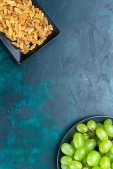 Bovenaanzicht gedroogde rozijnen in zwarte vorm met verse groene druiven op lichtblauwe achtergrond.