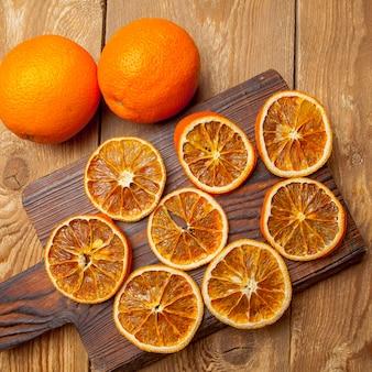 Bovenaanzicht gedroogde sinaasappel op snijplank en verse sinaasappelen op houten tafel