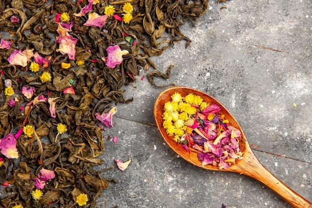 Bovenaanzicht gedroogde verse thee op het grijze houten bureau