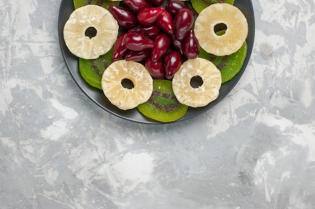 Bovenaanzicht gedroogde vruchten ananas ringen en kiwi plakjes op witte achtergrond fruit drogen zoete suiker zuur