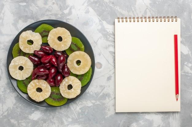 Bovenaanzicht gedroogde vruchten ananas ringen en kiwiplakken op lichte witte achtergrond fruit droge zoete suiker zuur