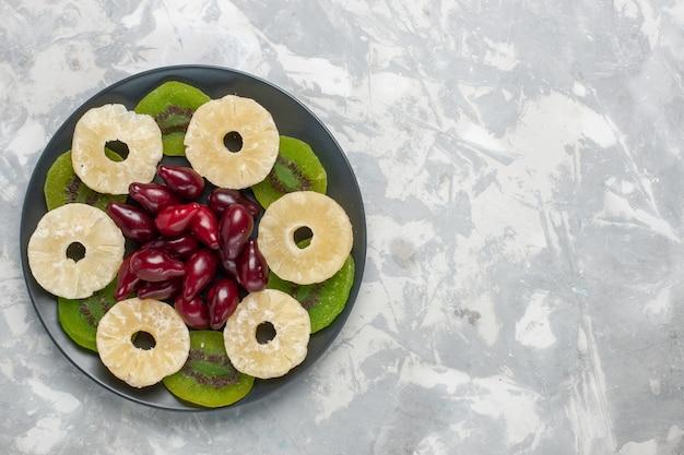 Bovenaanzicht gedroogde vruchten ananas ringen en plakjes kiwi op de witte achtergrond fruit droge zoete suiker zuur