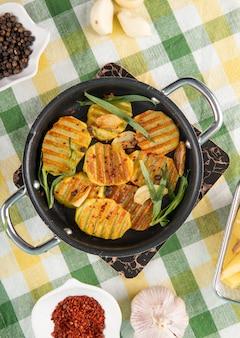 Bovenaanzicht gegrilde aardappelen met zwarte peper groene knoflook en gedroogde chili vlokken op het tafelkleed