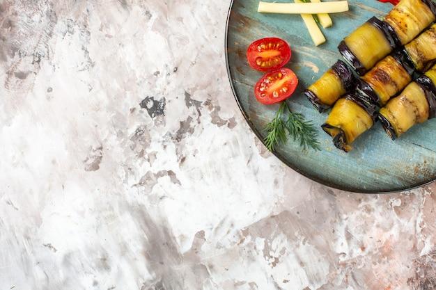 Bovenaanzicht gegrilde aubergine rolt tomaten op bord op naakt met vrije ruimte