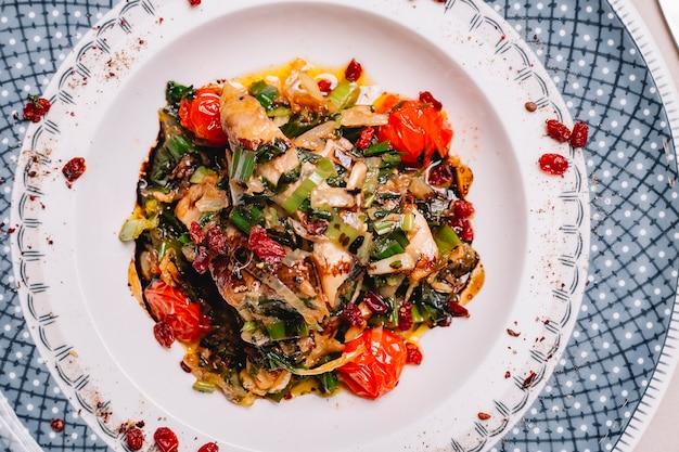 Bovenaanzicht gegrilde chickien met gebakken ui tomaten paprika en groenen op een bord