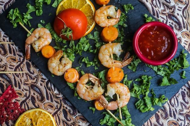 Bovenaanzicht gegrilde garnalen op spiesjes met wortelen tomatenkruiden en saus op een stand