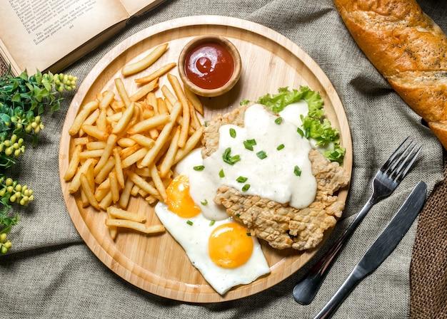 Bovenaanzicht gegrilde kipfilet met saus gebakken ei ketchup lente-ui sla en frietjes op een bord
