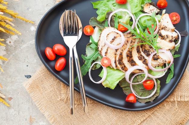 Bovenaanzicht. gegrilde kipsalade met tomaten en uien op zwarte plaat