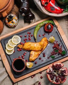 Bovenaanzicht gegrilde vis met tomaat en gegrilde hete peper met plakjes granaatappel-citroen en narsharab saus