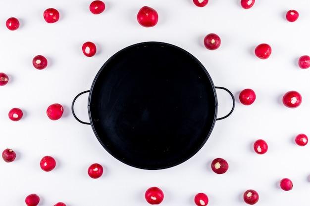 Bovenaanzicht geïsoleerd verse rode radijs met zwarte pan