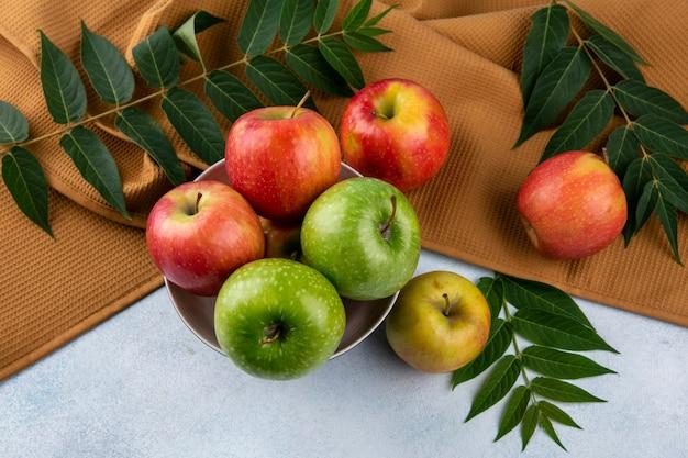 Bovenaanzicht gekleurde appels in een kom met bladtakken op een bruine handdoek op een grijze achtergrond