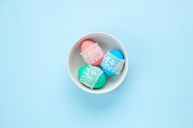 Bovenaanzicht gekleurde beschilderde eieren binnen plaat op blauw oppervlak sierlijke kleurrijke lente concept etnische Premium Foto