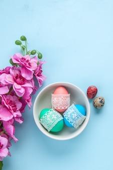 Bovenaanzicht gekleurde beschilderde eieren binnen plaat op blauw oppervlak vakantie kleurrijke lente etnische sierlijke
