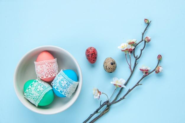 Bovenaanzicht gekleurde beschilderde eieren binnen plaat op blauw oppervlak vakantie lente concept etnische sierlijke