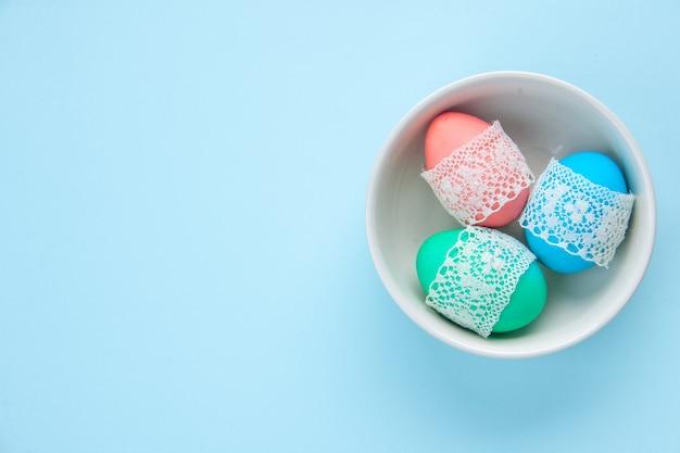 Bovenaanzicht gekleurde beschilderde eieren binnen plaat op blauwe oppervlakte vakantie kleurrijke lente concept etnische sierlijke