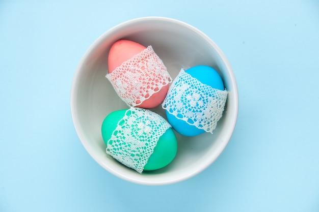 Bovenaanzicht gekleurde beschilderde eieren binnen plaat op blauwe oppervlakte vakantie sierlijke kleurrijke lente concept etnische