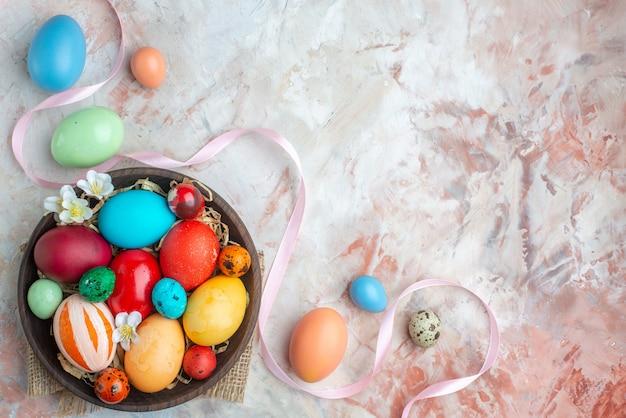 Bovenaanzicht gekleurde beschilderde eieren binnen plaat op witte achtergrond suiker kleurrijke novruz zoete lente vakantie dessert sierlijke