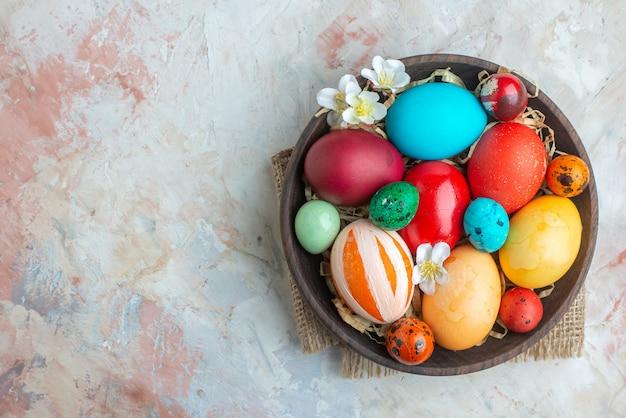 Bovenaanzicht gekleurde beschilderde eieren binnen plaat op witte achtergrond suiker kleurrijke sierlijke zoete lente vakantie dessert