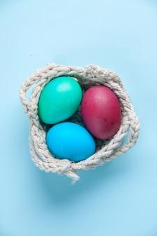 Bovenaanzicht gekleurde beschilderde eieren binnen touwen op blauwe oppervlakte vakantie kleurrijke lente concept etnische sierlijke