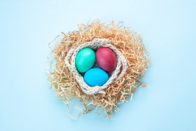 Bovenaanzicht gekleurde beschilderde eieren in geel stro en touwen op blauw oppervlak vakantie kleurrijk lenteconcept etnisch sierlijk