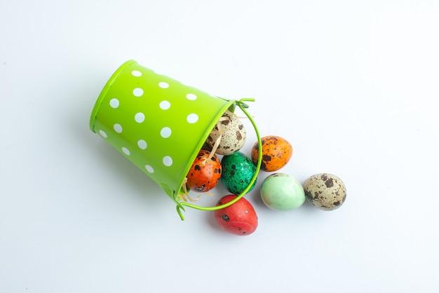 Bovenaanzicht gekleurde beschilderde eieren in groene mand op witte achtergrond sierlijke lente kleurrijke concept vakantie horizontaal