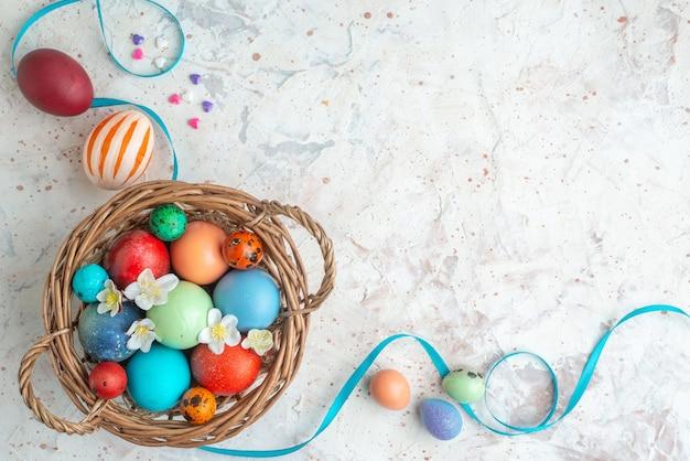 Bovenaanzicht gekleurde beschilderde eieren in mand op witte achtergrond novruz sierlijke lente horizontale vakantie concept kleurrijk