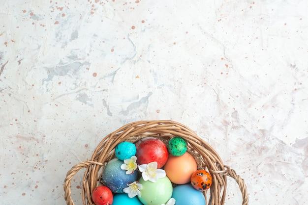 Bovenaanzicht gekleurde beschilderde eieren in mand op witte achtergrond novruz sierlijke lente kleurrijke horizontale concept