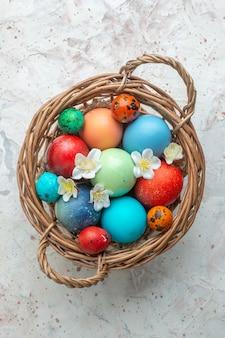 Bovenaanzicht gekleurde beschilderde eieren in mand op witte achtergrond novruz sierlijke lente kleurrijke horizontale vakantie concept