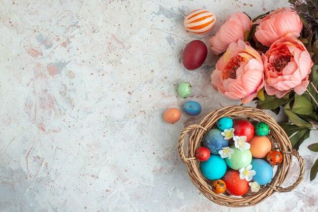 Bovenaanzicht gekleurde beschilderde eieren in mand op witte achtergrond novruz sierlijke lente vakantie concept kleurrijk
