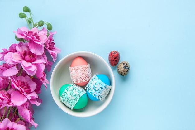 Bovenaanzicht gekleurde beschilderde eieren in plaat op blauw oppervlak vakantie kleurrijk concept etnisch sierlijk Premium Foto