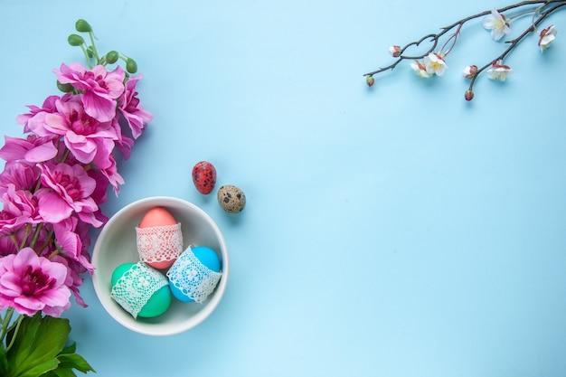 Bovenaanzicht gekleurde beschilderde eieren in plaat op blauw oppervlak vakantie kleurrijk lenteconcept etnisch