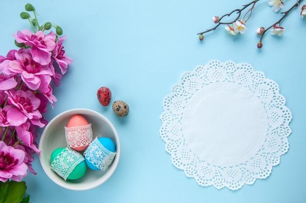 Bovenaanzicht gekleurde beschilderde eieren in plaat op blauw oppervlak vakantie kleurrijk lenteconcept sierlijk