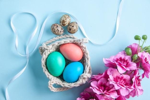Bovenaanzicht gekleurde beschilderde eieren in touwen op blauw oppervlak vakantie kleurrijk lenteconcept sierlijk