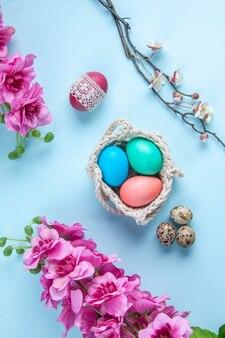 Bovenaanzicht gekleurde beschilderde eieren in touwen op blauwe ondergrond etnische sierlijke lente concept vakantie kleurrijk