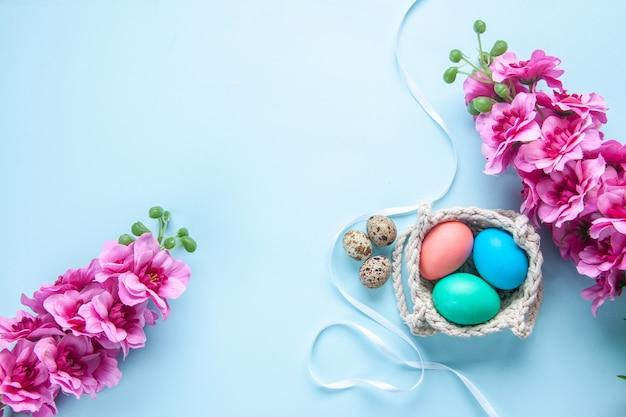 Bovenaanzicht gekleurde beschilderde eieren in touwen op blauwe ondergrond kleurrijke lente etnische sierlijke vakantie